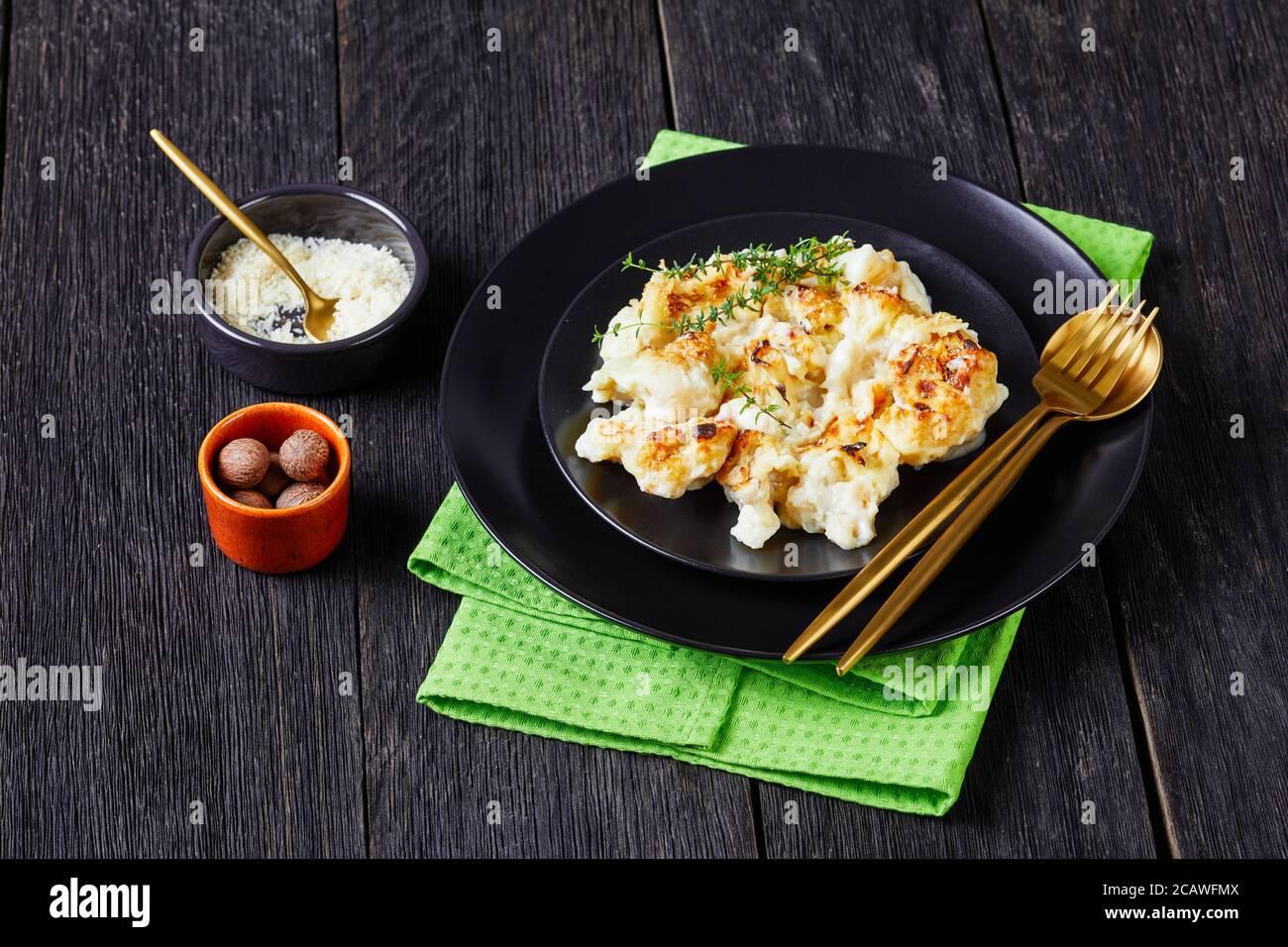 Cocotte de chou-fleur servie sur une assiette noire avec thym frais sur fond de bois avec muscade, parmesan râpé et couverts, Banque D'Images