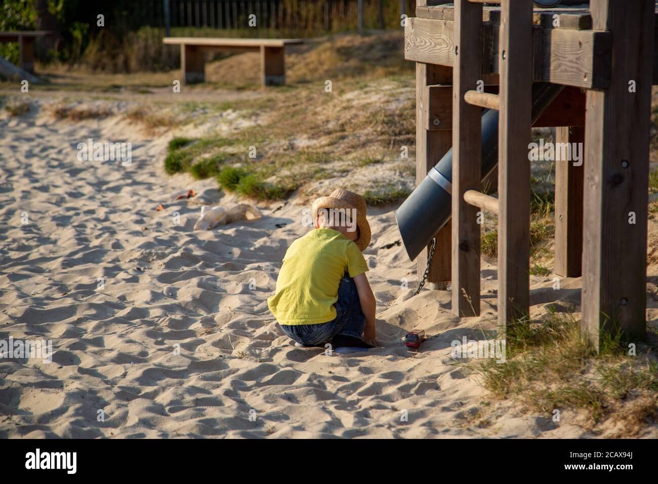Un petit garçon jouant dans un bac à sable dans un parc pendant l'été avec un cadre d'escalade en vue Banque D'Images