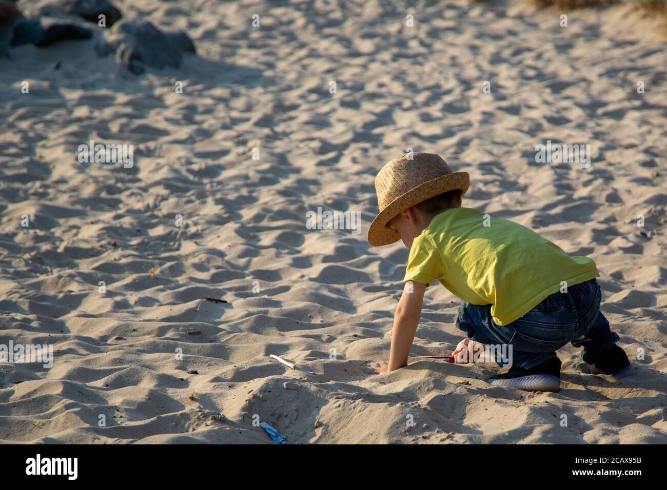Un petit garçon jouant dans un bac à sable dans un parc en été Banque D'Images