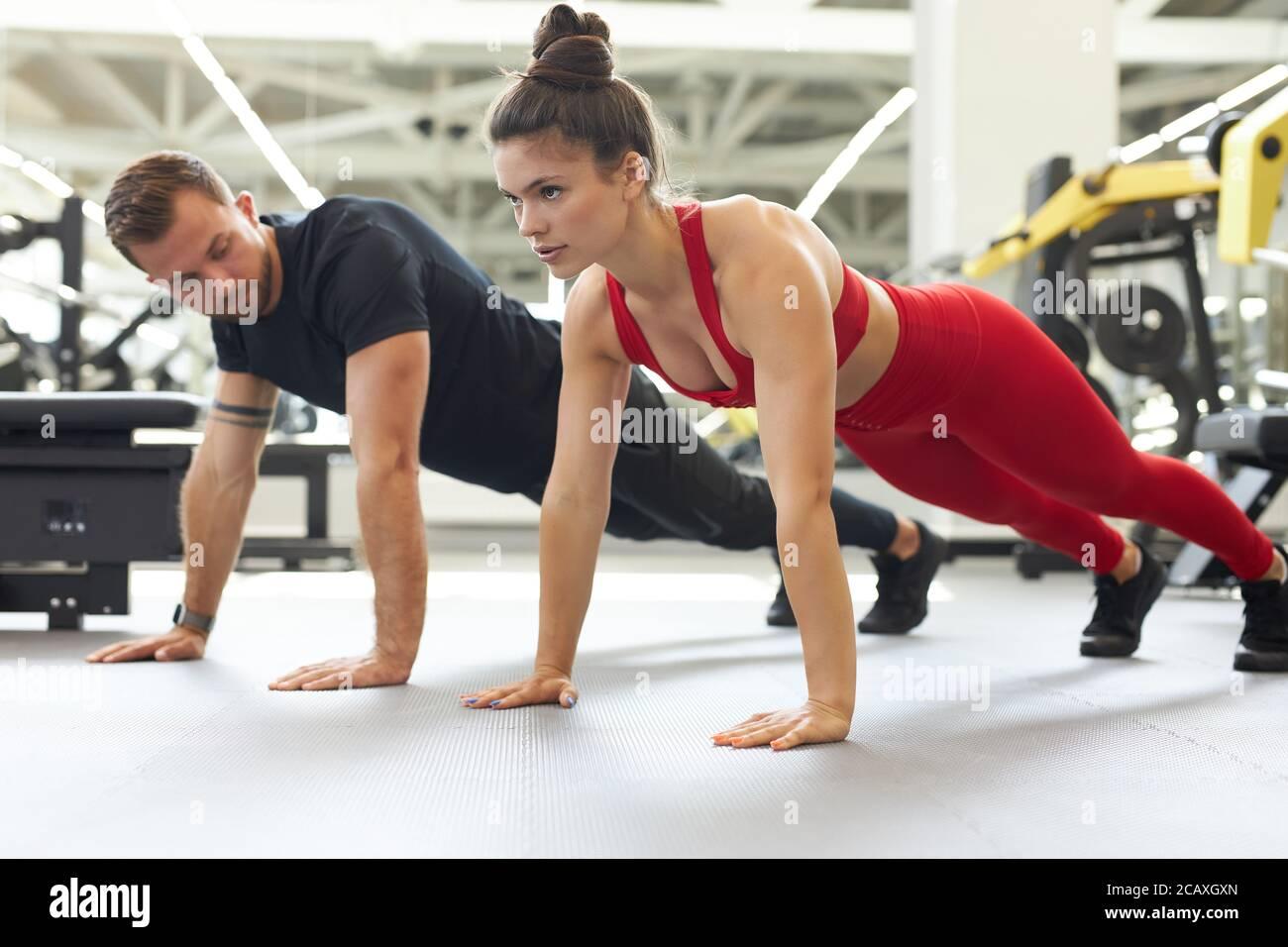 magnifique jeune couple fort qui fait des push-up ensemble dans la salle de gym. vue latérale Banque D'Images