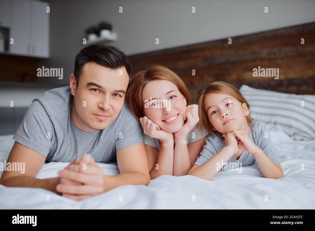 portrait de belle famille heureuse couché sur le lit ensemble, mère père et fille de kid embrassant embrassant et rire. à l'intérieur Banque D'Images