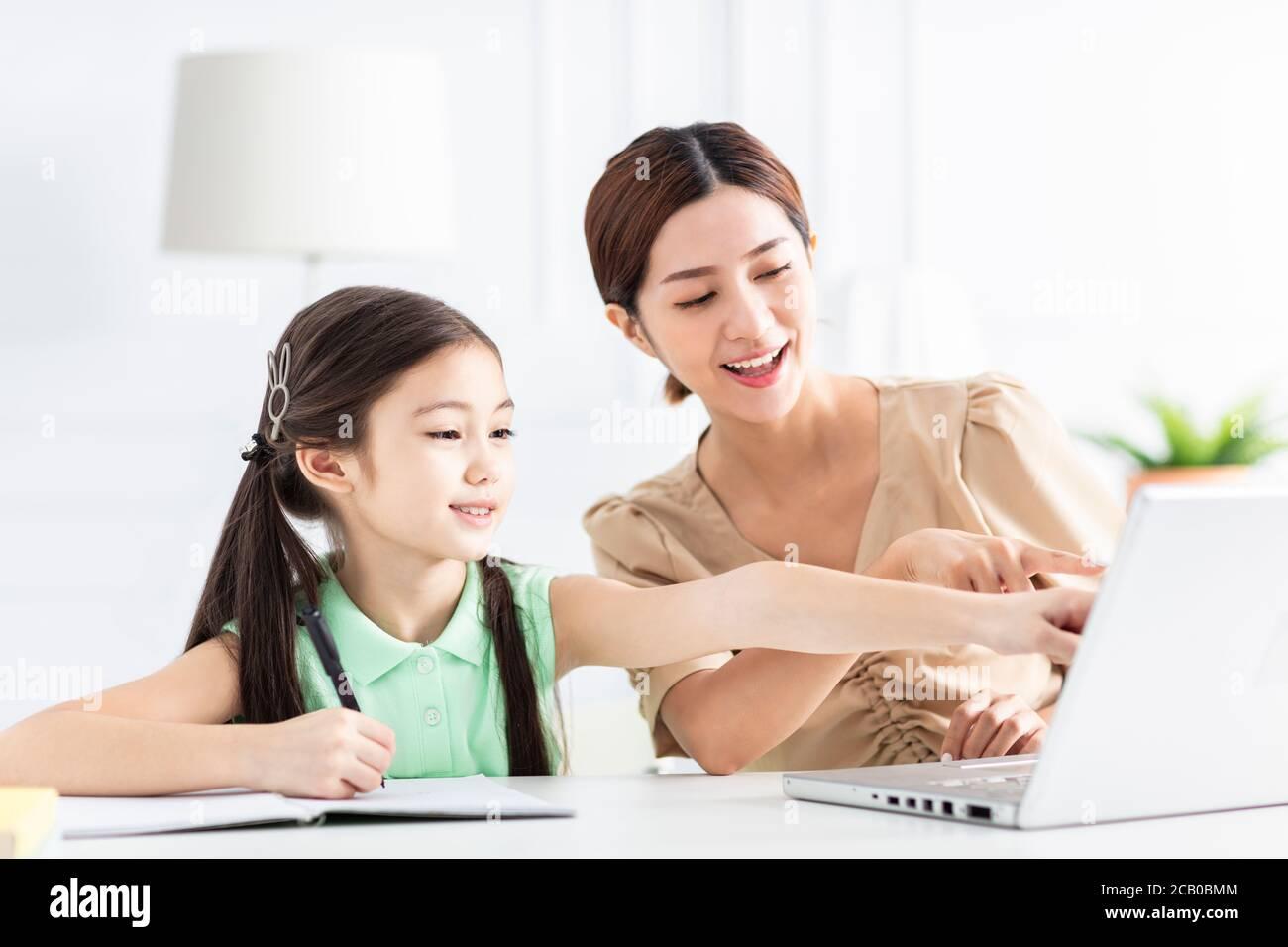 Mère avec fille regardant l'ordinateur portable et travaillant à la maison Banque D'Images