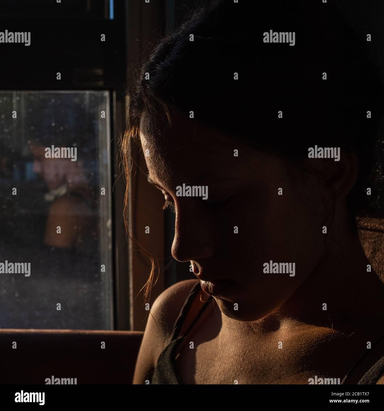 Portrait de la belle fille brune dans l'obscurité avec une lumière douce sur son visage, silhouette pensive regardant vers le bas, un reflet sur la fenêtre. Banque D'Images