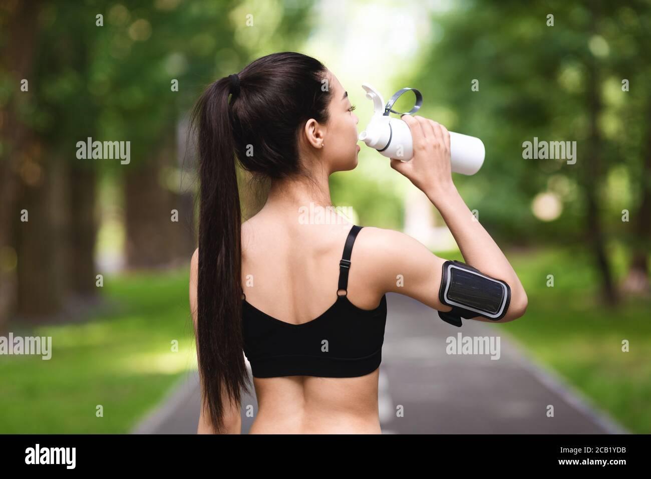 Vue arrière de la femme de fitness asiatique qui boit de l'eau après le jogging dans le parc Banque D'Images