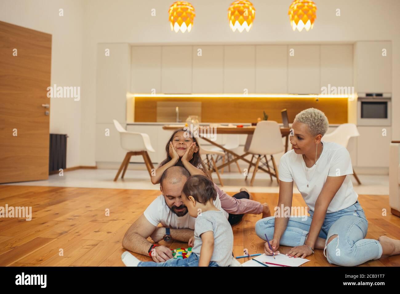 Famille s'amuser ensemble dans le salon de la maison. Maman, papa et deux enfants sur le sol dessin, rire, jouer. Happy Family concept Banque D'Images