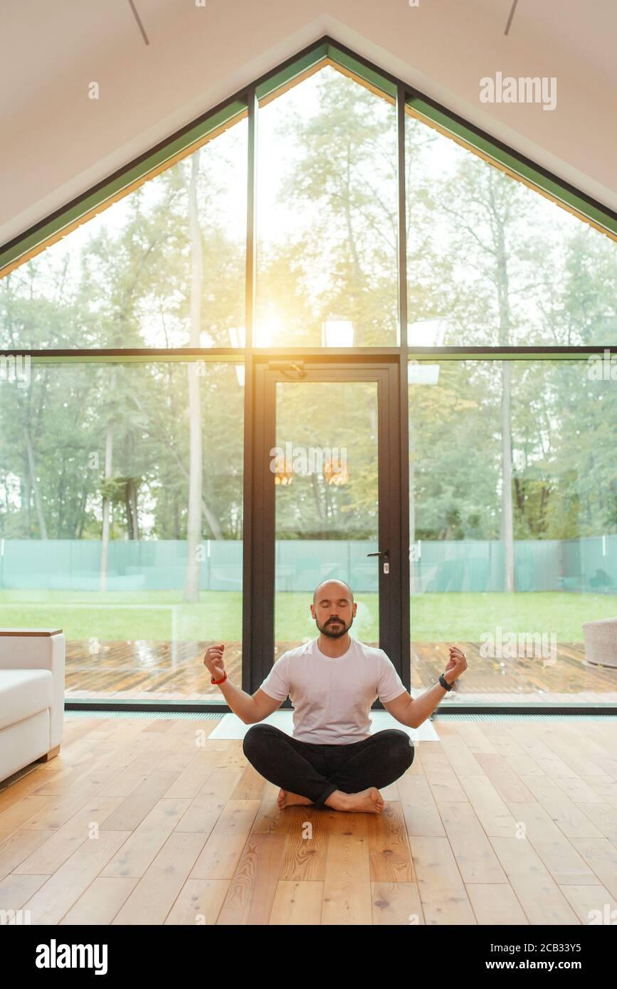 Homme dans des vêtements décontractés assis en position lotus méditer, se détendre. Arrière-plan grande fenêtre panoramique. Yoga à la maison concept Banque D'Images