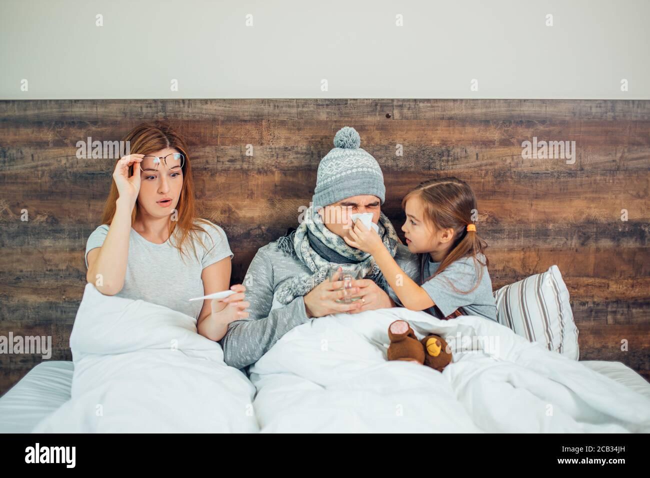 famille caucasienne malade, couchée au lit ensemble, souffrant de maladie. Un homme, une femme et une fille malsains se traitant à la maison Banque D'Images