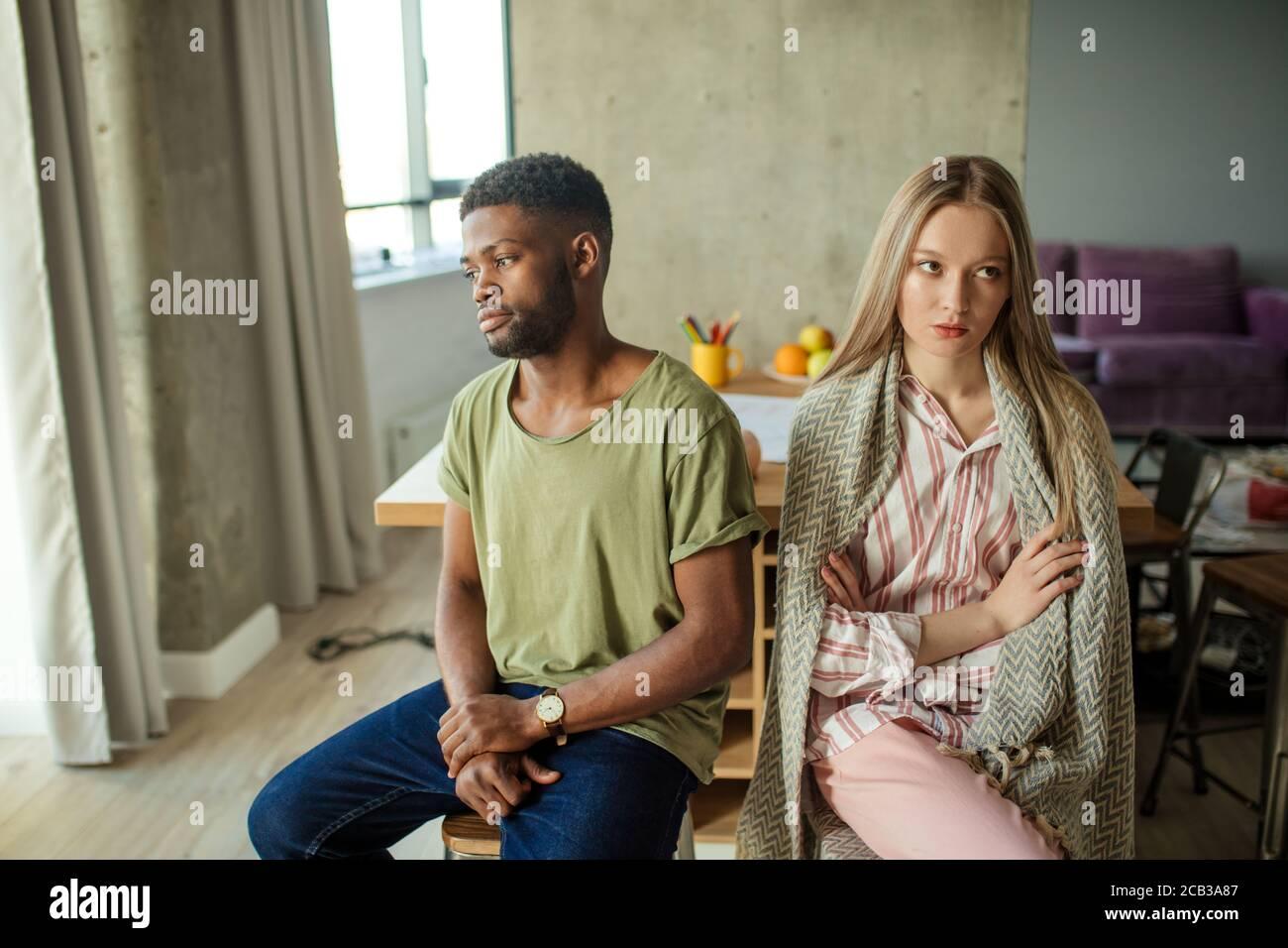 Jeune couple interracial malheureux ayant des problèmes dans la relation, assis dans la salle de séjour à la maison Banque D'Images