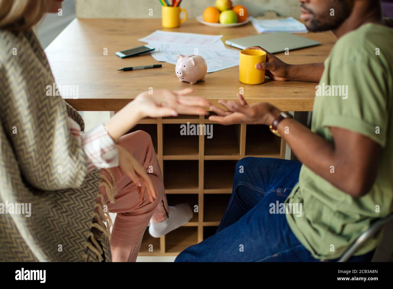 Un petit cliché de couple multiethnique a un peu de malentendu, exprimer cette condition par un geste de main perplexe, tout en étant assis à la table dans livi Banque D'Images