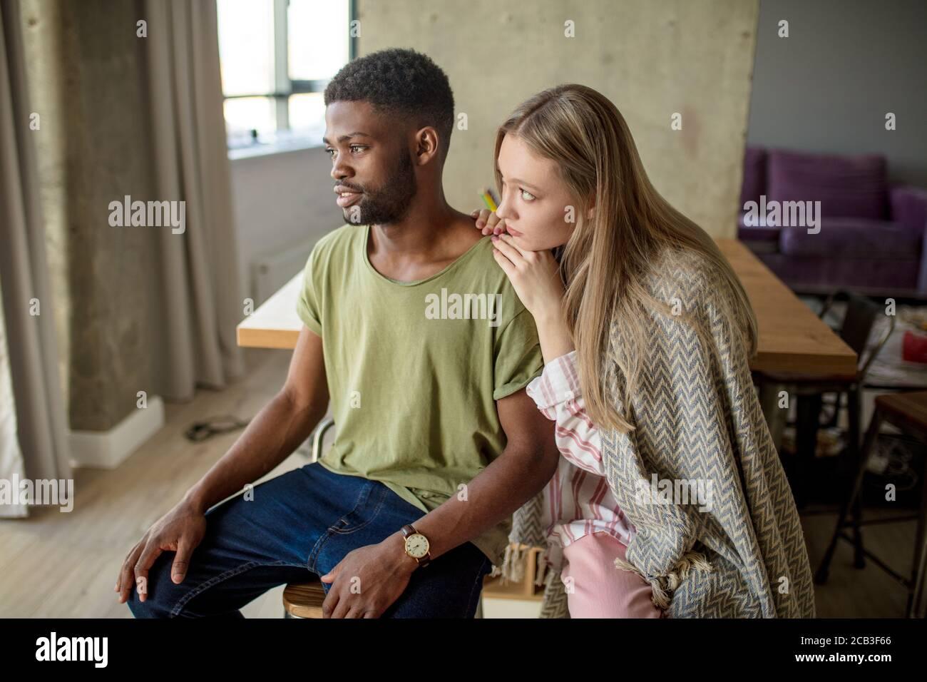 La femme blonde caucasienne consoles et soutient son ami hippster africain, qui a le regard sombre et frustré, le couple est assis dans la vie confortable Banque D'Images