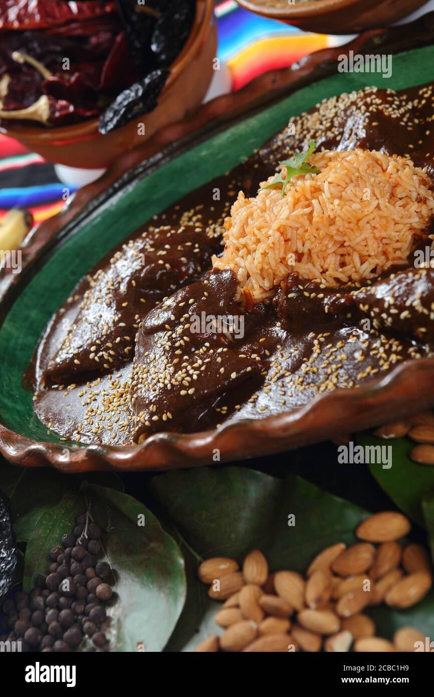 Gros plan de délicieux poulet recouvert de sauce à la mole avec du riz autour des noix, du chocolat et des épices Banque D'Images