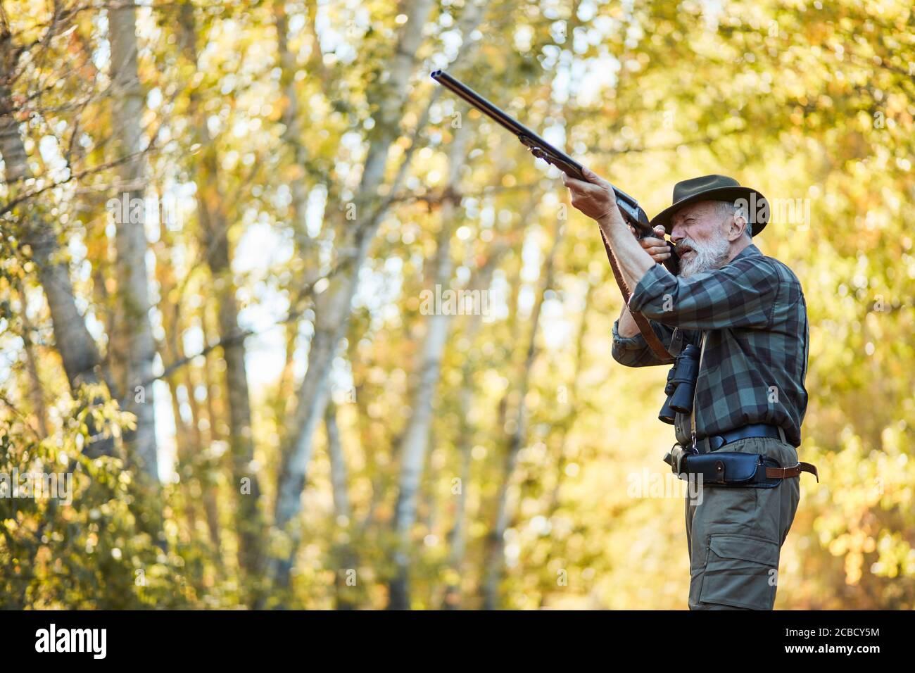 Un chasseur de haut niveau vise le trophée oiseau dans la forêt d'automne, pointant le fusil sur l'oiseau. Banque D'Images