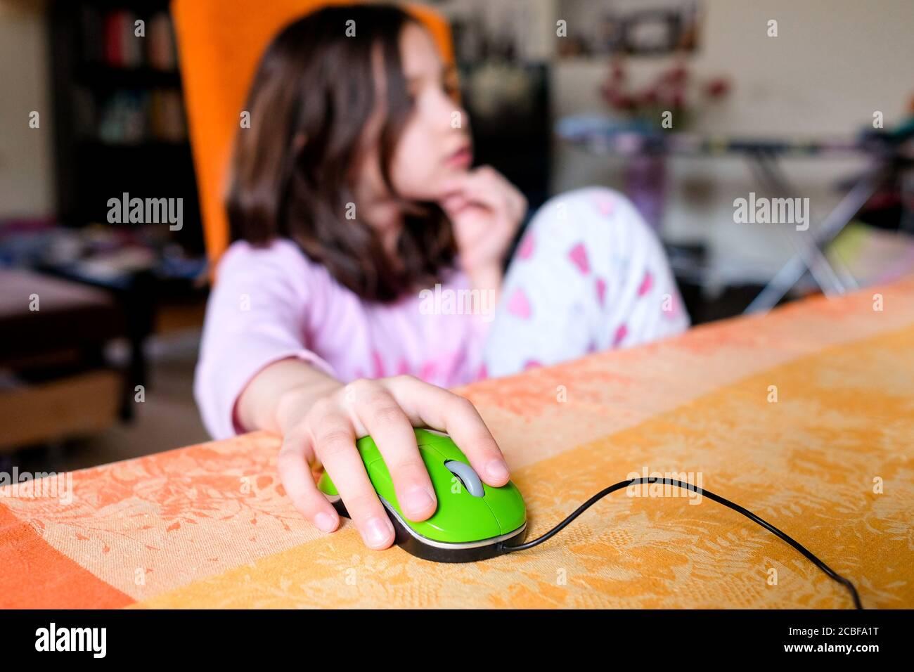 La fille contrôle la souris d'ordinateur. L'enfant est assis sur une chaise à la maison. Étudier à la maison. Banque D'Images