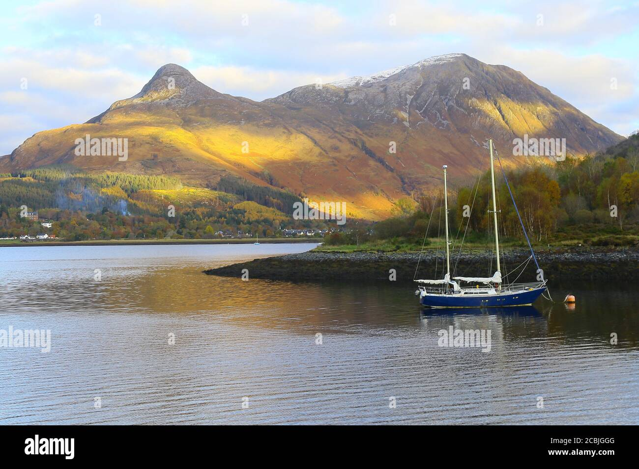 Montagnes écossaises avec un bateau bleu sur le loch. Banque D'Images