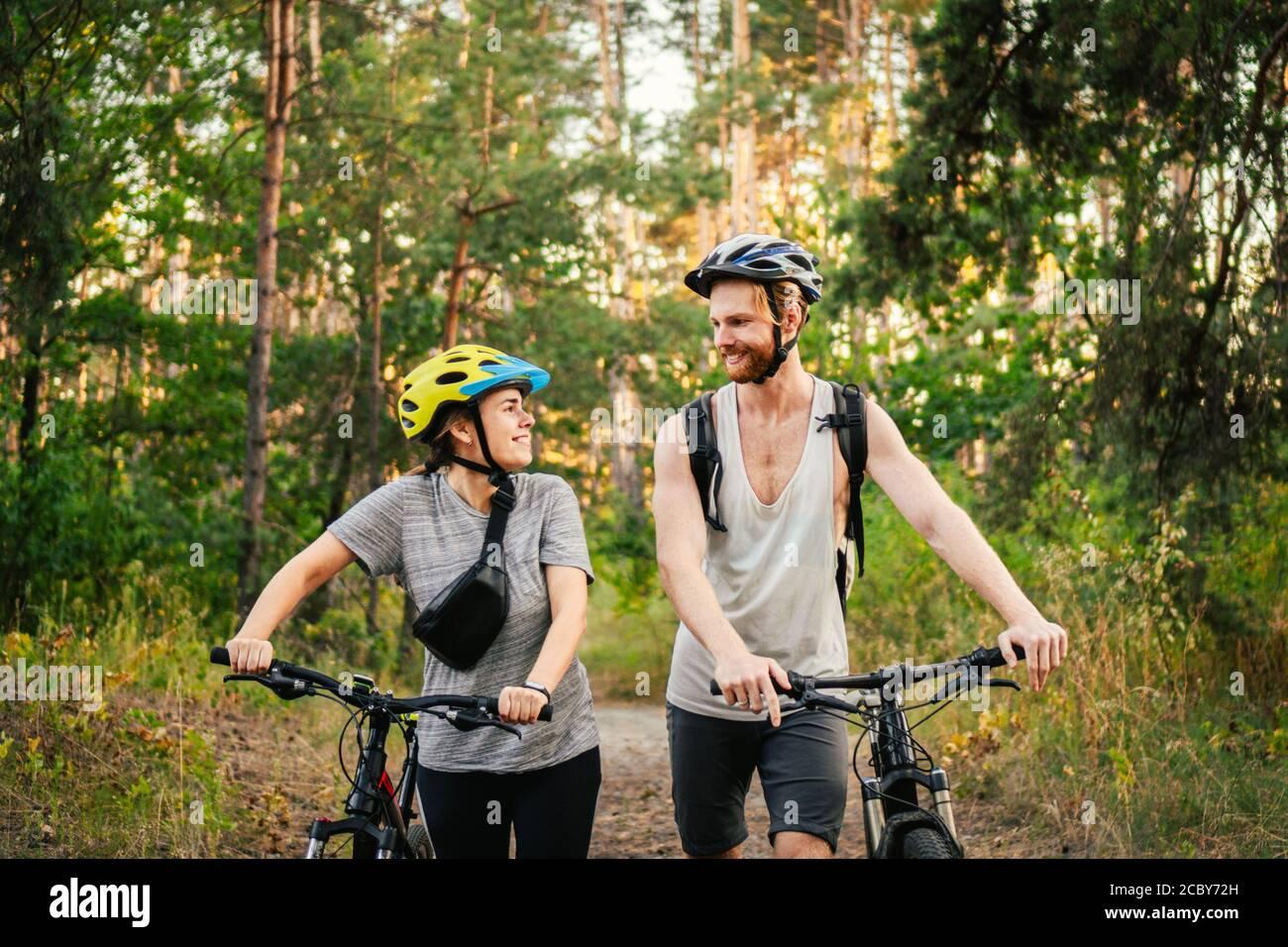 Couple joyeux poussant des vélos et marchant le long de la route de la forêt. Couple heureux avec vélo de marche dans le parc et de parler et rire. Caucasien Banque D'Images
