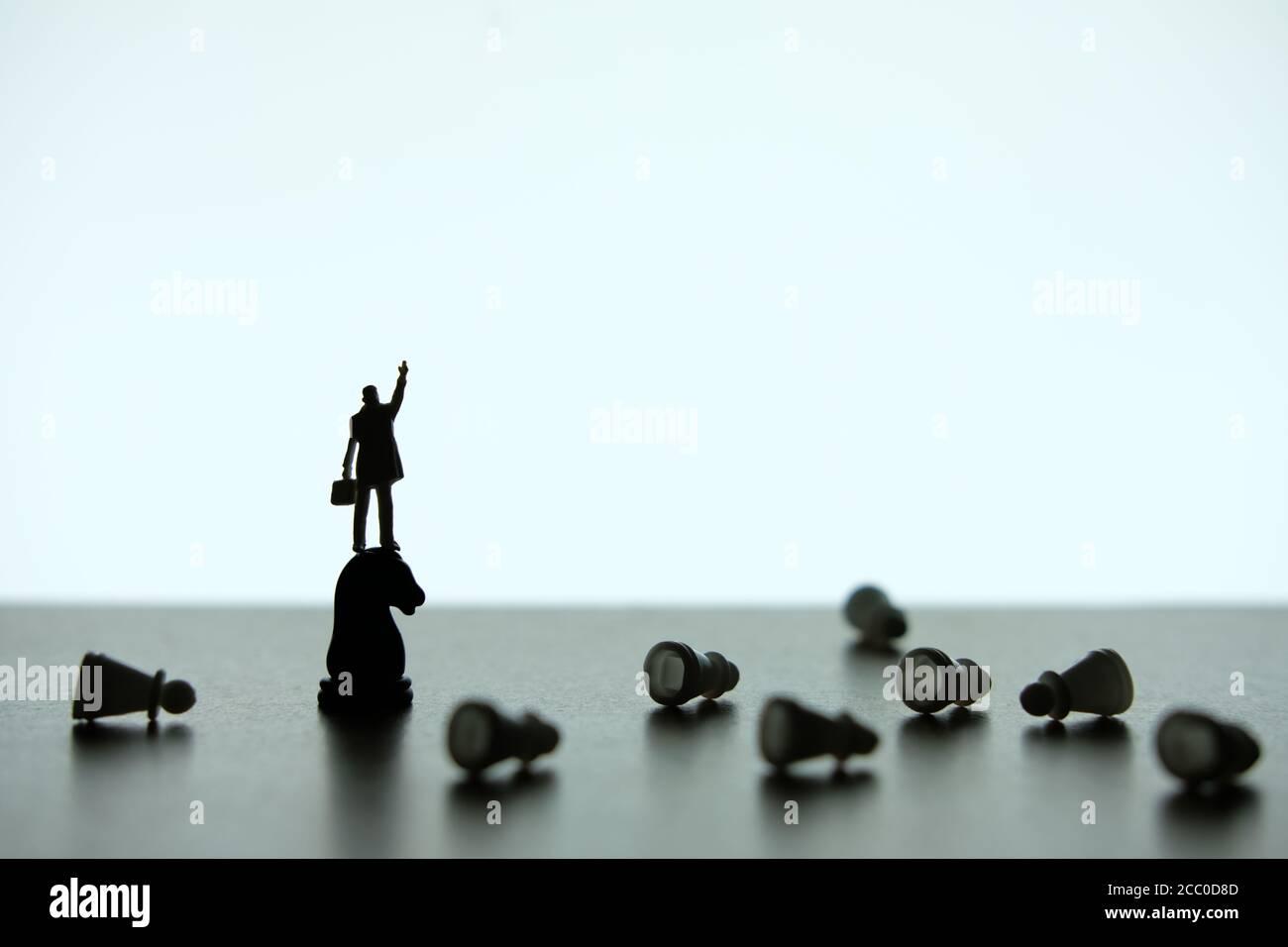 Photo conceptuelle de stratégie d'affaires - Silhouette d'homme d'affaires miniature pointant à l'envers, debout sur un morceau de cheval d'échecs Banque D'Images