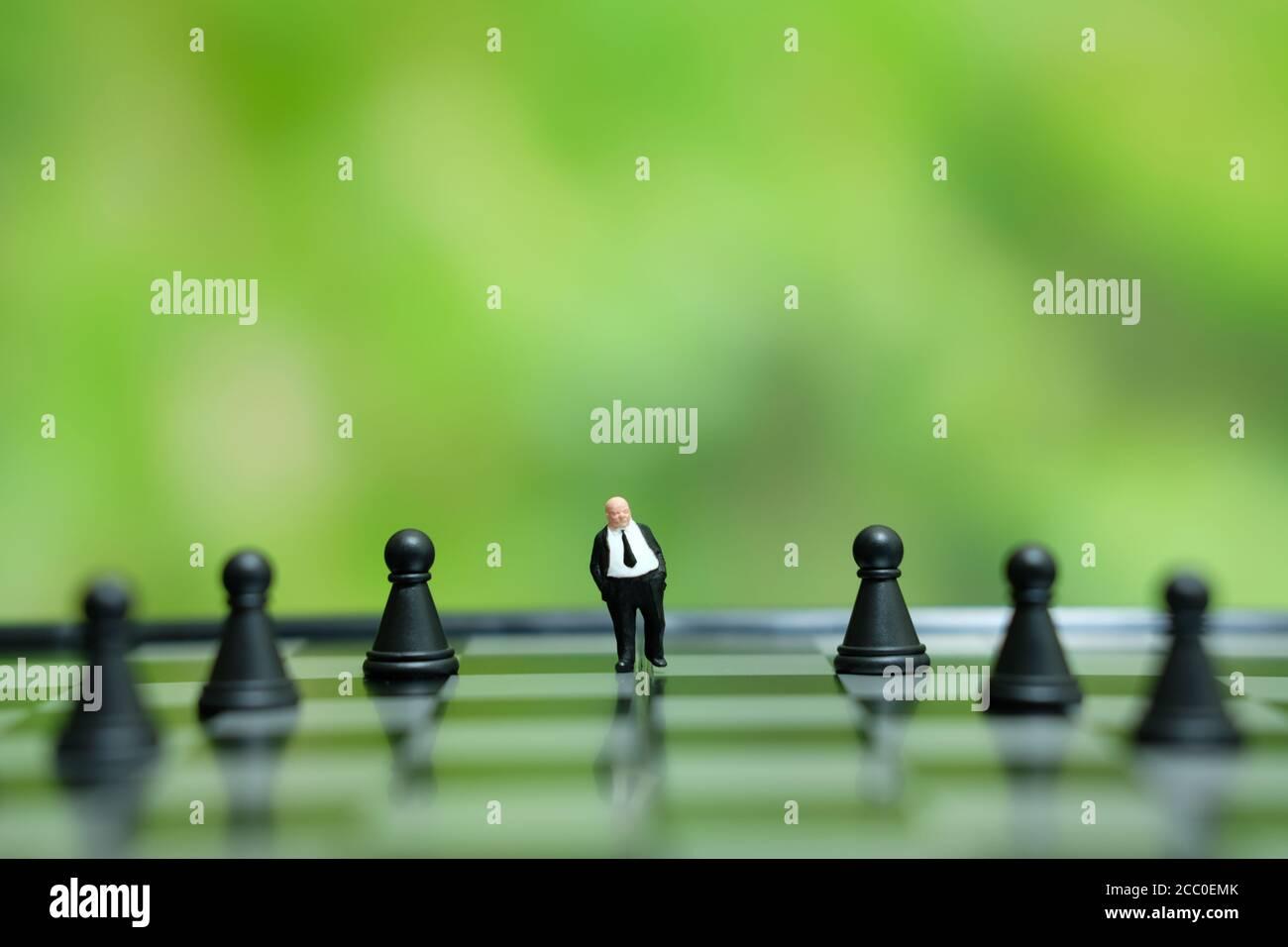 Photo conceptuelle de la stratégie d'affaires - miniature de l'homme d'affaires debout le milieu d'une pièce d'échecs sur un échiquier Banque D'Images