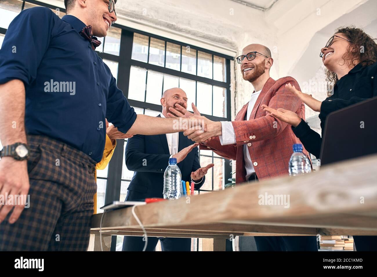 Poignée de main de l'entreprise lors d'une réunion ou d'une négociation au bureau. Les partenaires sont satisfaits parce qu'ils signent un contrat ou des documents financiers. Attention sélective Banque D'Images