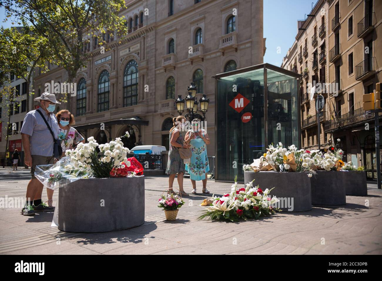 Les personnes portant des masques de visage observent les hommages aux victimes de l'attaque de Barcelone.trois ans après l'attaque de Barcelone, un hommage aux victimes est rendu à Las Ramblas. Banque D'Images
