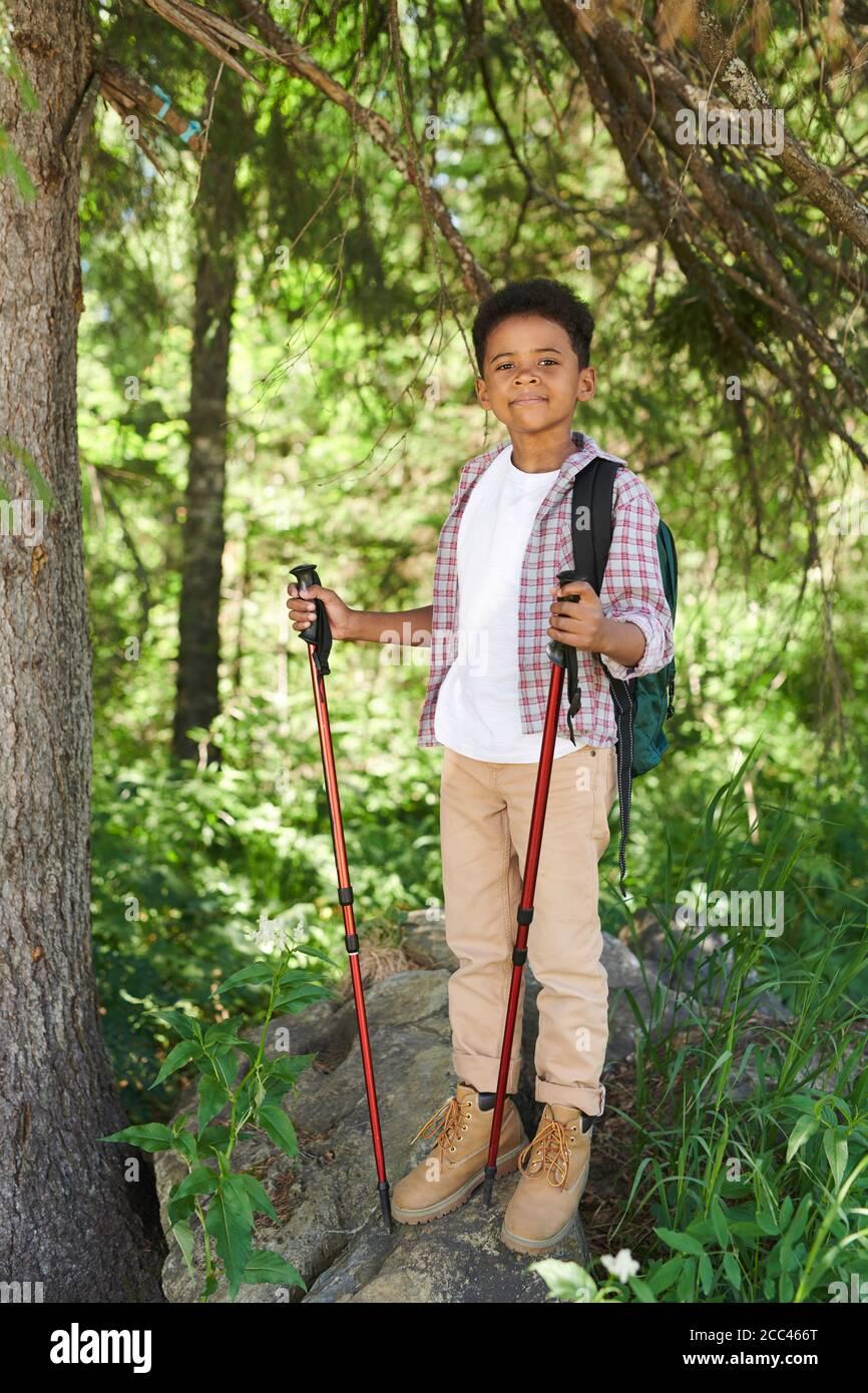 Portrait d'un garçon africain debout avec des bâtons et regardant appareil photo pendant son voyage dans la forêt Banque D'Images