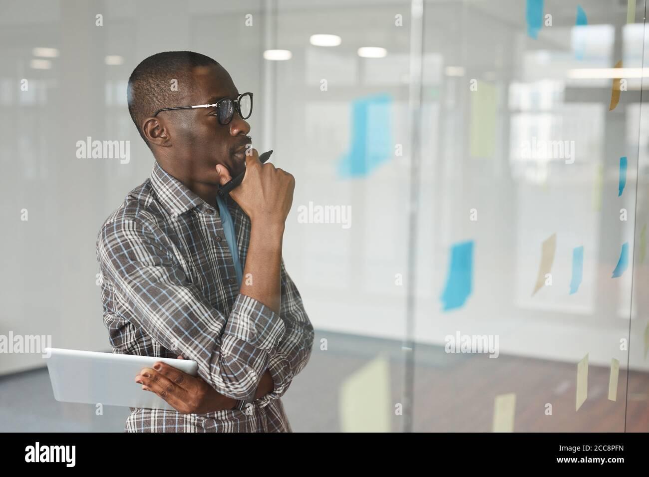 Homme d'affaires africain pensif en lunettes debout devant le verre et en regardant les notes adhésives qu'il pense sur les nouvelles idées Banque D'Images