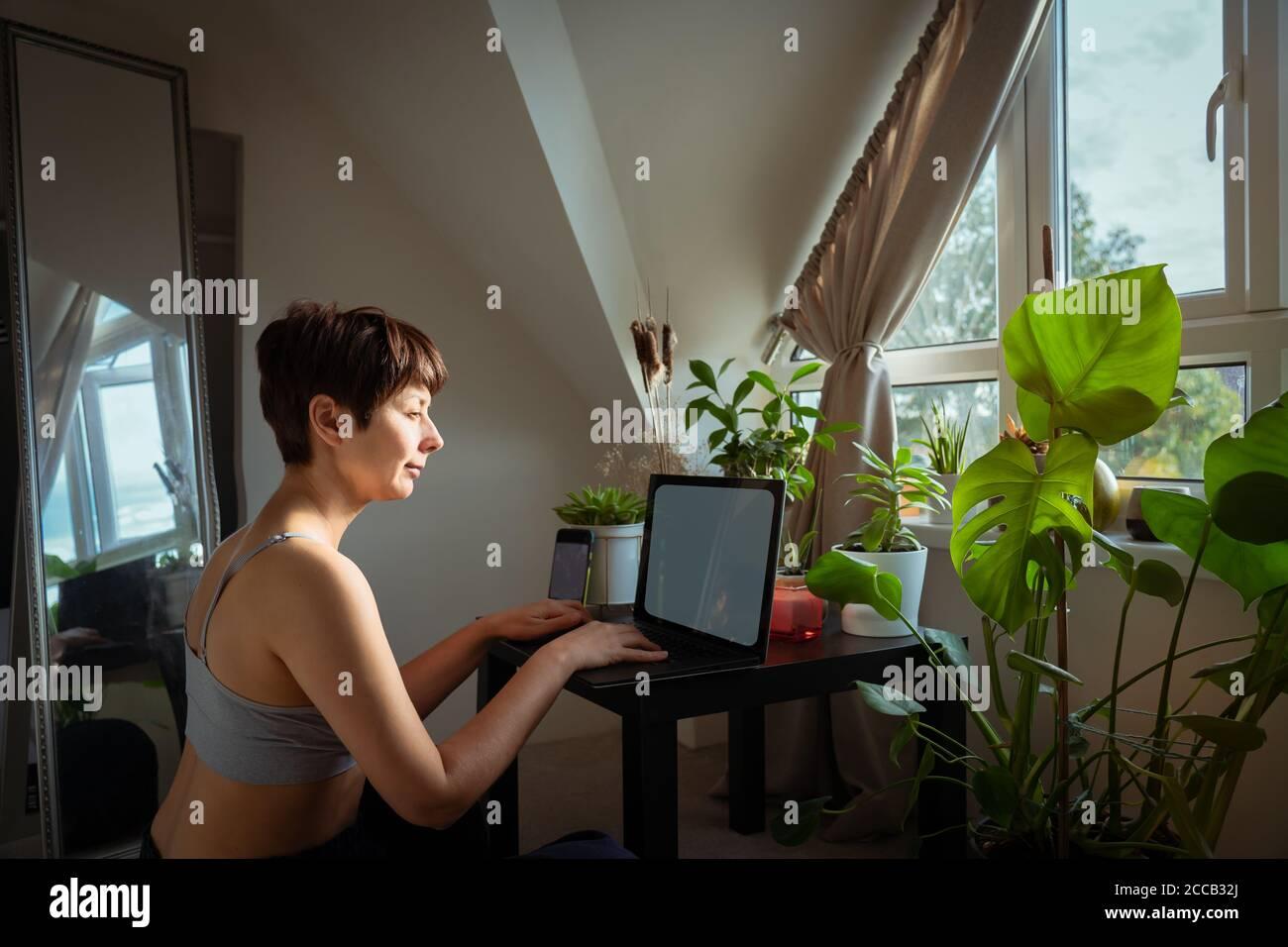 Femme de course mixte dans des vêtements de maison décontractés travaillant sur un ordinateur portable assis à une table basse avec beaucoup de plantes vertes en pot près de la fenêtre. Travailler à la maison Banque D'Images