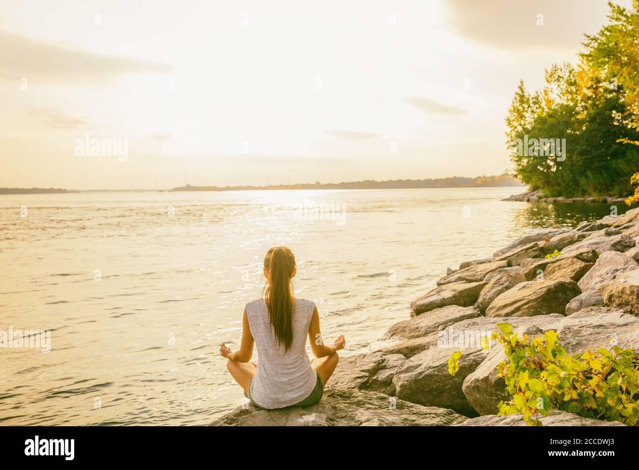 Cours de yoga à l'extérieur dans un parc naturel près du bord du lac. Une femme assise dans le lotus pose méditant par l'eau dans le soleil du matin se fait jour au lever du soleil. Méditation Banque D'Images