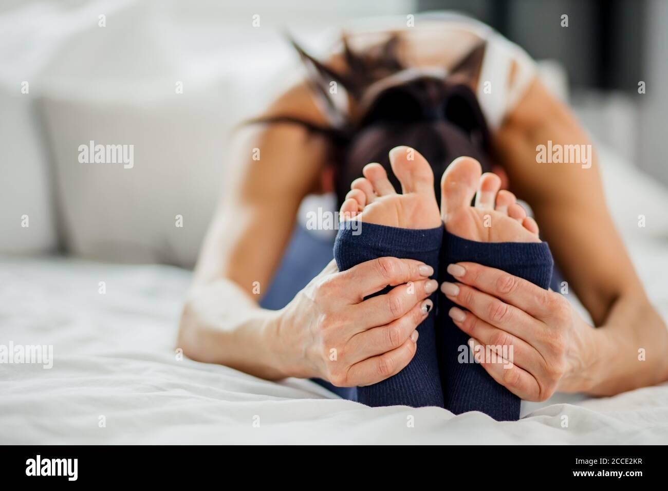 photo en gros plan des jambes de la jeune femme tout en s'étirant sur le lit à la maison, mode de vie sain et concept de yoga Banque D'Images