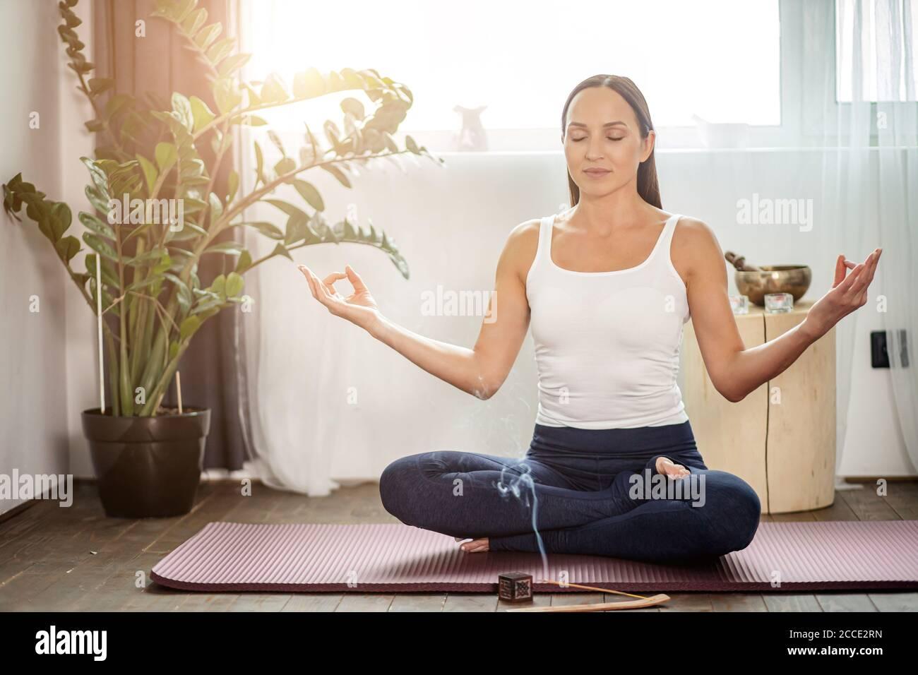 calme yogi femelle s'asseoir sur le sol dans la pose de lotus, méditer à la maison pendant la quarantaine, chaque matin commence du yoga, elle utilise des bâtons d'arôme Banque D'Images