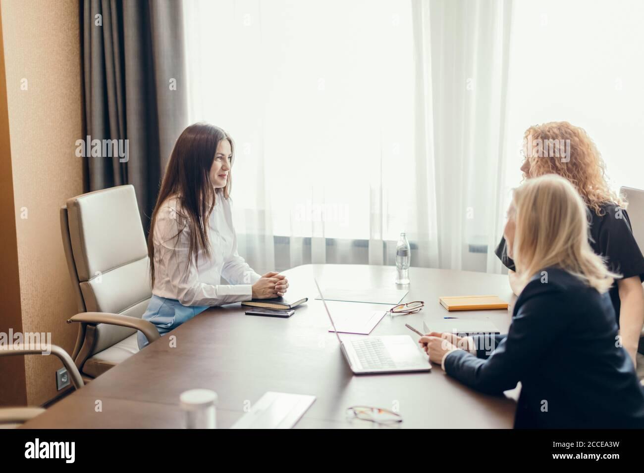 Deux femmes gestionnaires des ressources humaines menant une entrevue d'emploi avec une femme candidate au bureau. Obtenir un nouveau concept de poste Banque D'Images