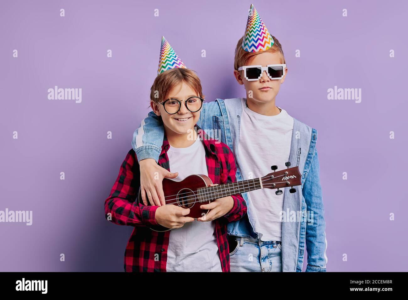 portrait de beaux garçons d'enfants à joyeux anniversaire portant un chapeau de vacances sur la tête et tenant ukulele, la musique d'exécution. amitié, enfants, cont anniversaire Banque D'Images