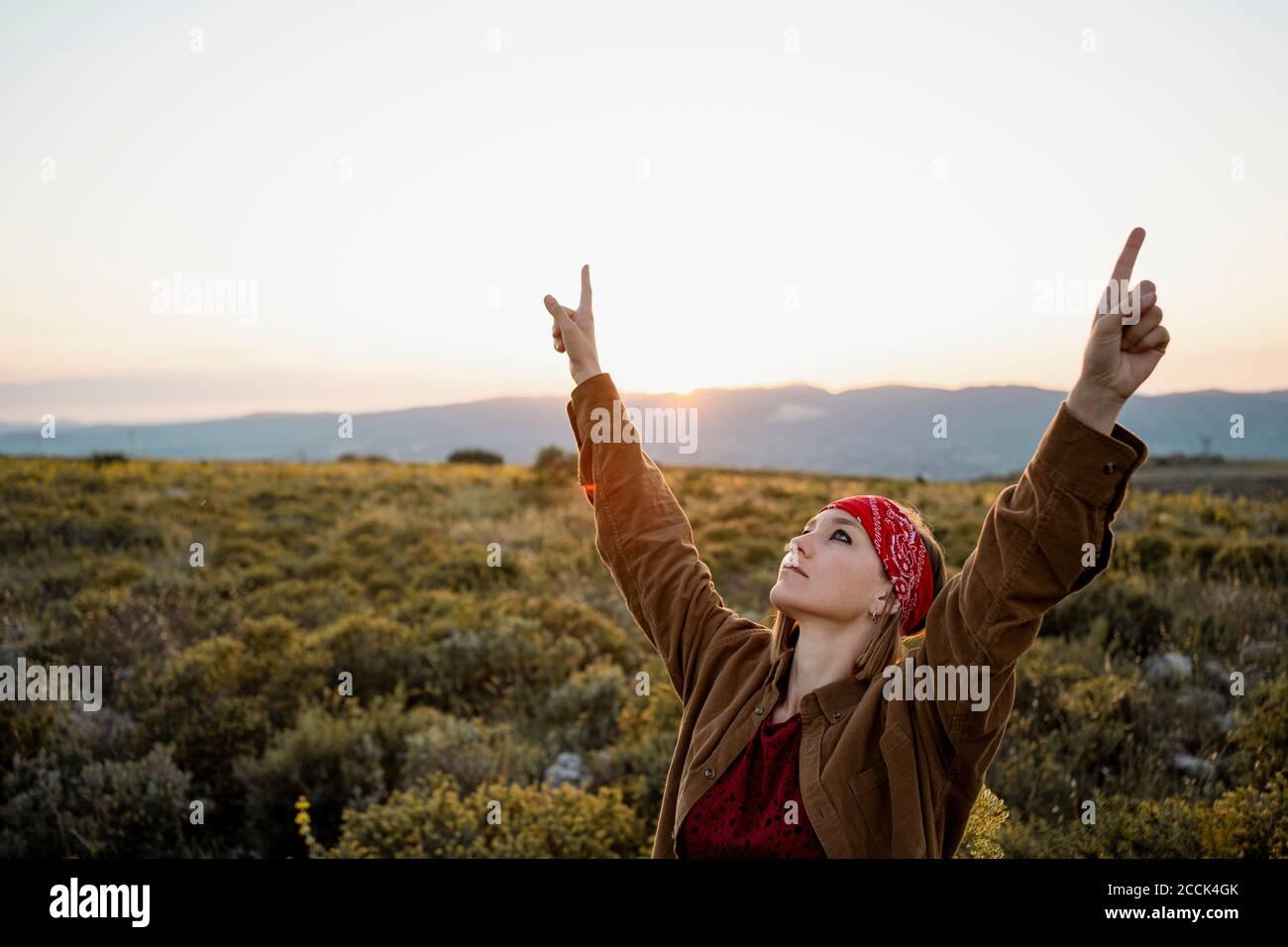 Femme aux bras levés dans la campagne regardant vers le haut Banque D'Images