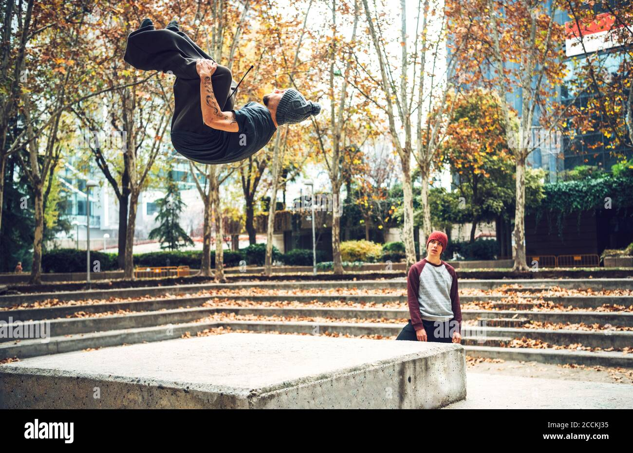 Un jeune homme sautant alors qu'un ami regarde dans un parc public Banque D'Images