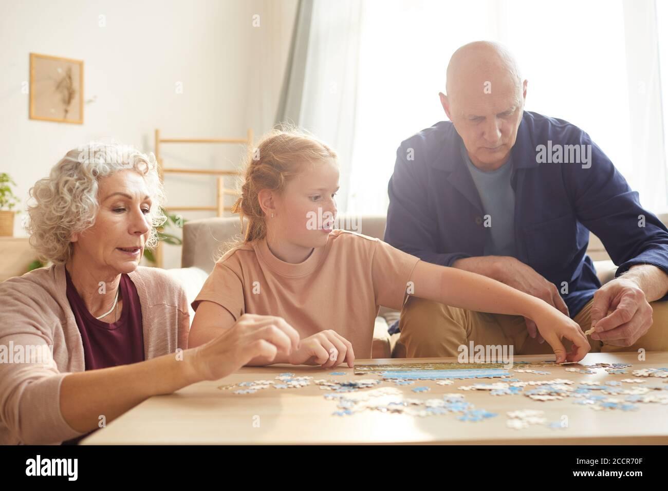 Portrait de cure fille à cheveux rouges jouant à des jeux de société avec grand-parents tout en appréciant le temps ensemble dans une maison confortable éclairée par lumière du soleil Banque D'Images
