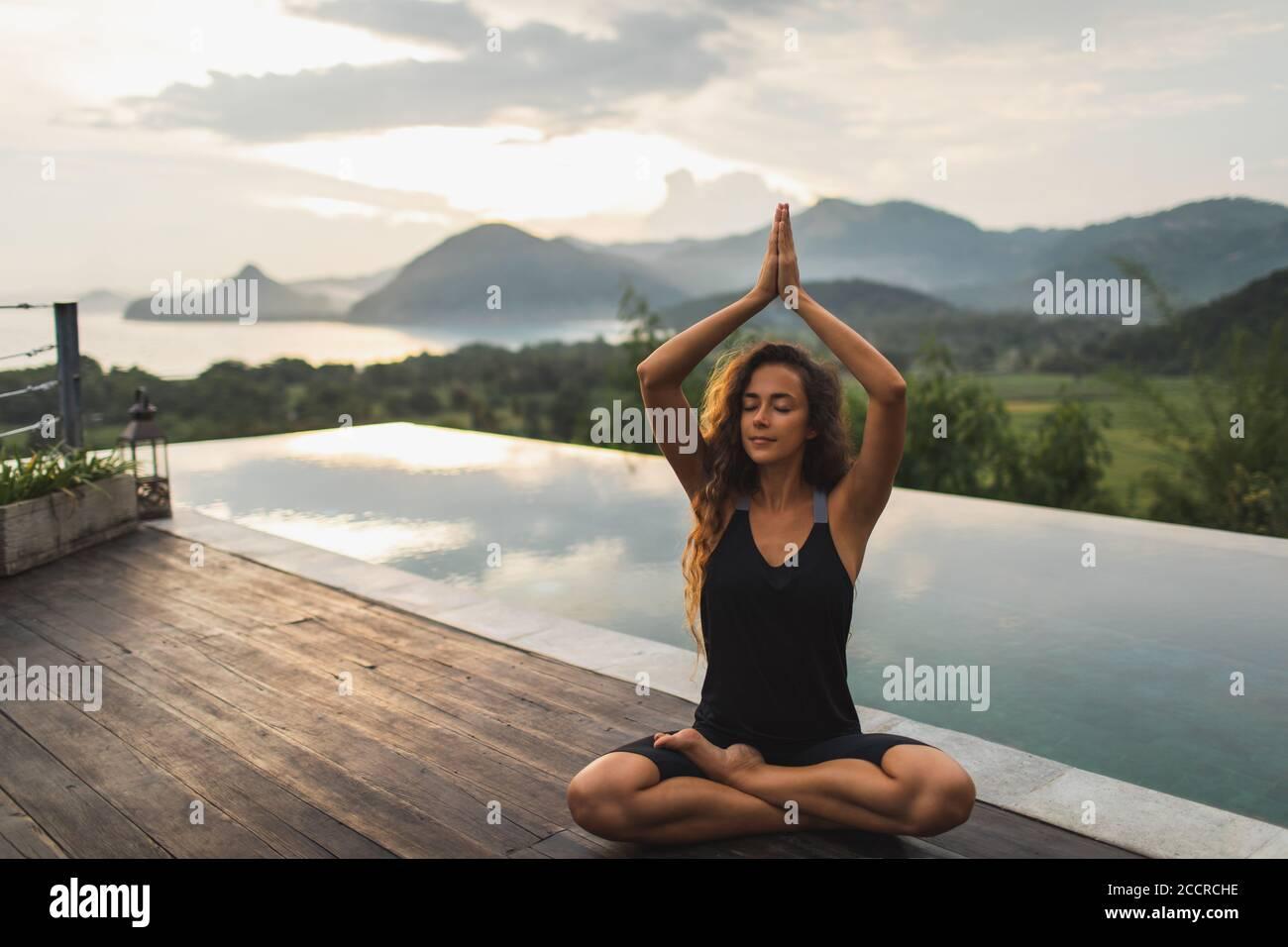 Femme méditant seule sur la piscine à débordement avec belle vue sur l'océan et la montagne le matin. Mode de vie sain, concept spirituel et émotionnel. Éveil, harmonie avec la nature. Banque D'Images