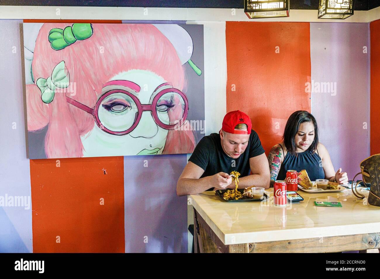 Floride Orlando East Central Park North Bumby Avenue Pom Pom's. Teahouse & Sandwicheria restaurant à l'intérieur homme femme couple manger des œuvres d'art décor Banque D'Images