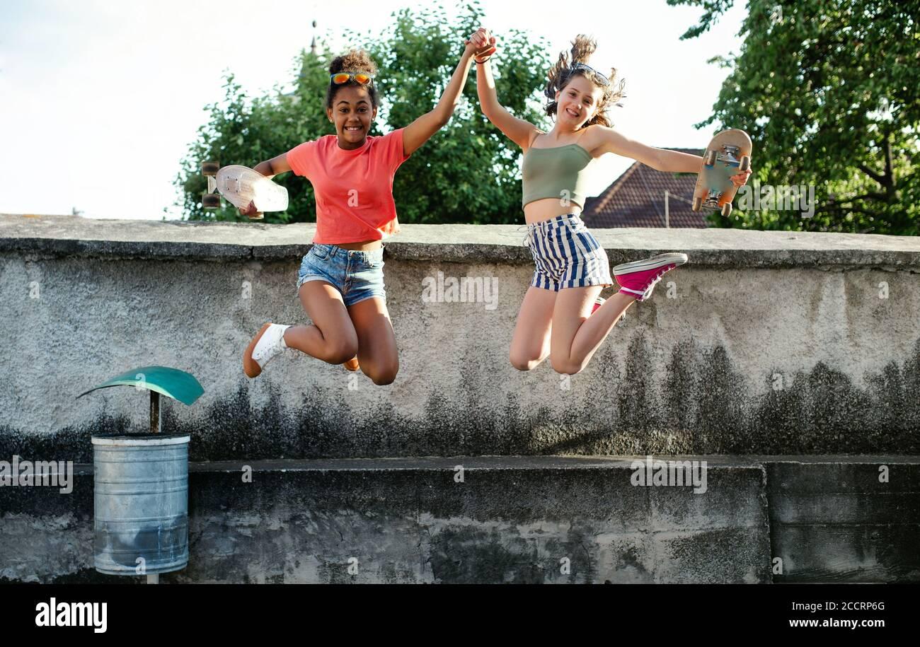 Jeunes adolescentes amies avec des planches à roulettes en plein air en ville, sautant. Banque D'Images