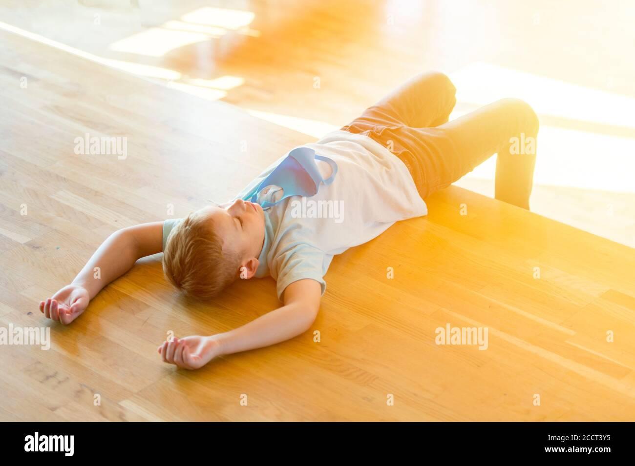 Enfant fatigué stressé épuisé avec masque bleu dans une leçon. Retour à l'école en toute sécurité pendant la pandémie concept. Distance sociale pour combattre COVID-19 Banque D'Images