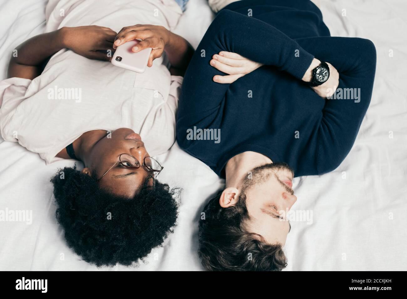 couple interracial allongé dans le lit, ayant des arguments les uns avec les autres dans la chambre à coucher. Une femme africaine attentionnés contrariée, stressée, veut exprimer son sentiment Banque D'Images