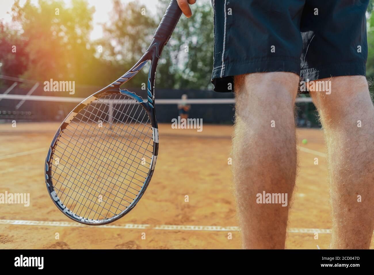 Gros plan de l'homme tenant une raquette en attendant le service de balle sur le court de tennis. L'homme est au premier plan et au premier plan, le filet de tennis est en arrière-plan et flou Banque D'Images