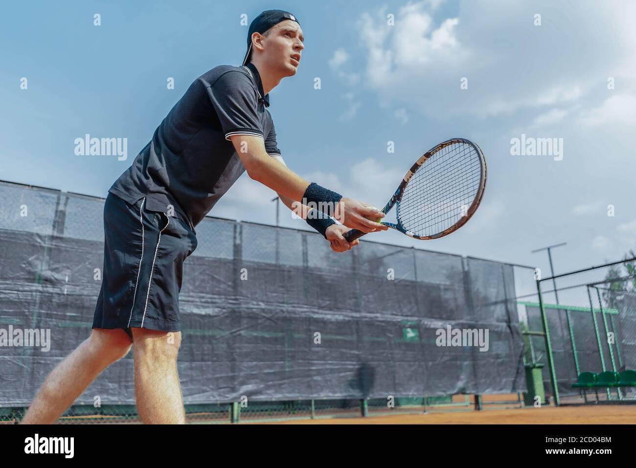 Le joueur de tennis Plan of Man à distance se prépare à servir une balle de tennis au match. Joueur tenant un ensemble dans les deux mains pour servir UNE balle avec une frappe droite Banque D'Images