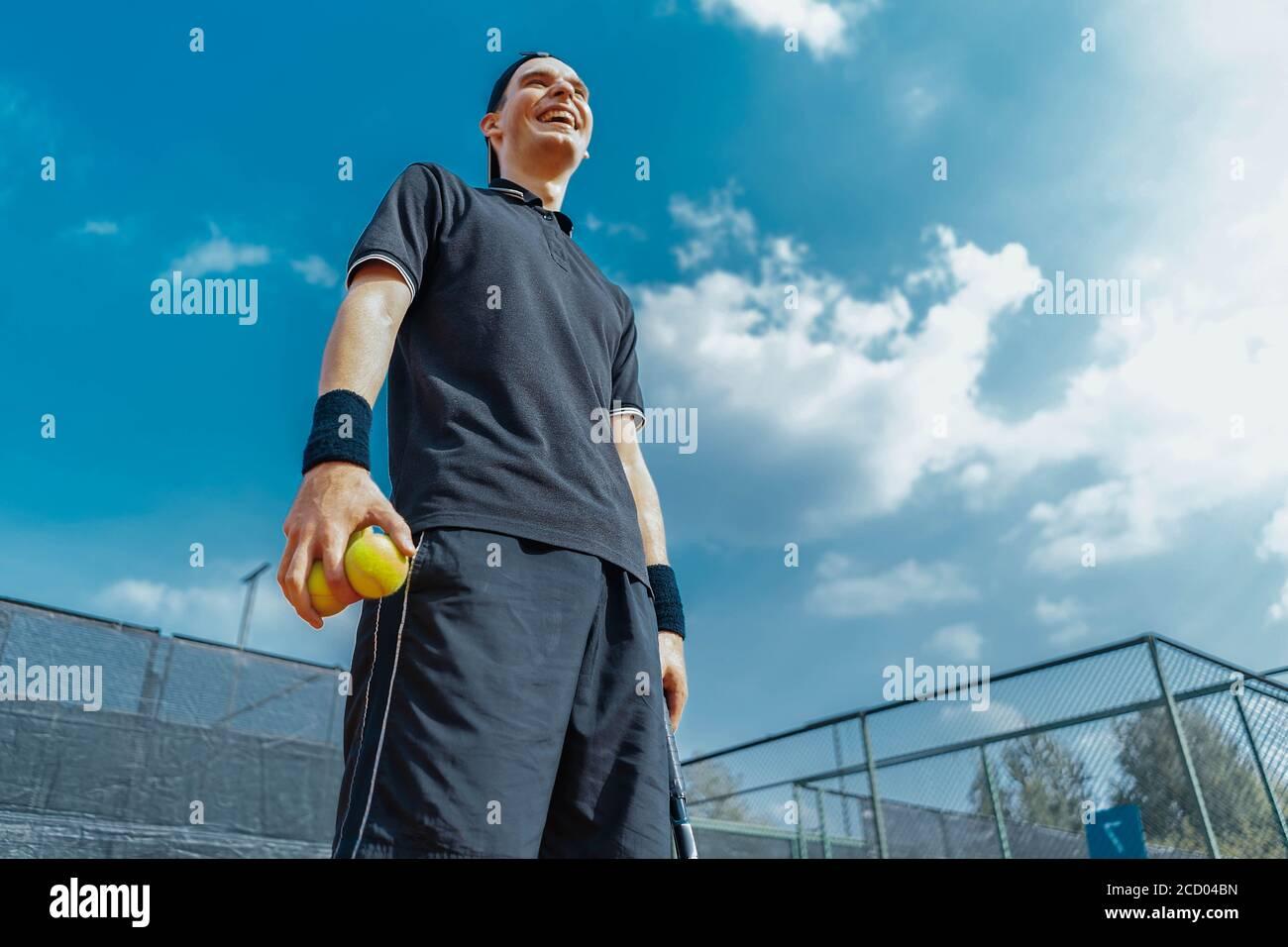 Gros plan sur Young attractive Man Laughung et détente après le tournoi et tenue de balles de tennis et raquette. Banque D'Images
