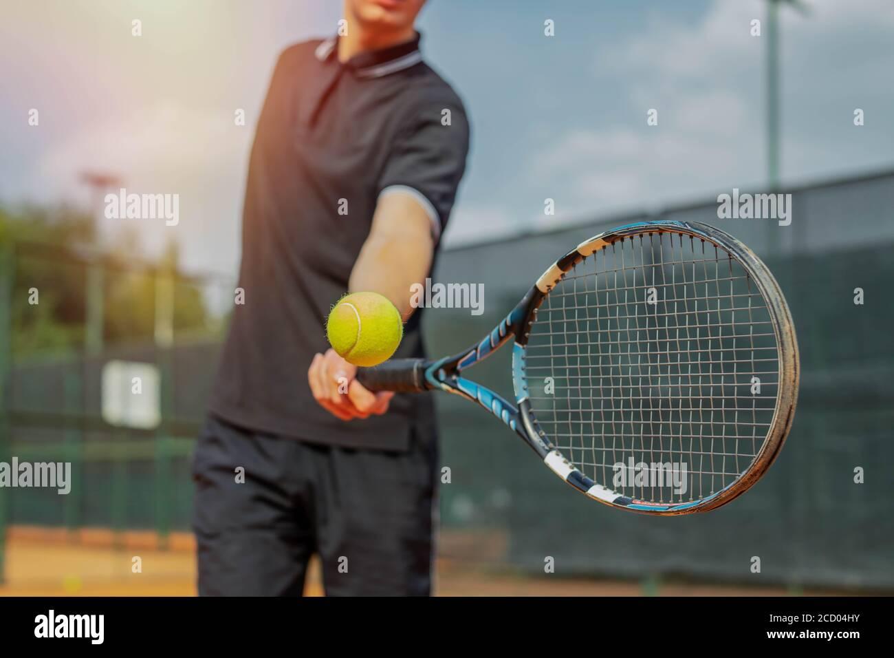 Gros plan sur un homme jouant au tennis et battant le ballon avec une raquette. Banque D'Images