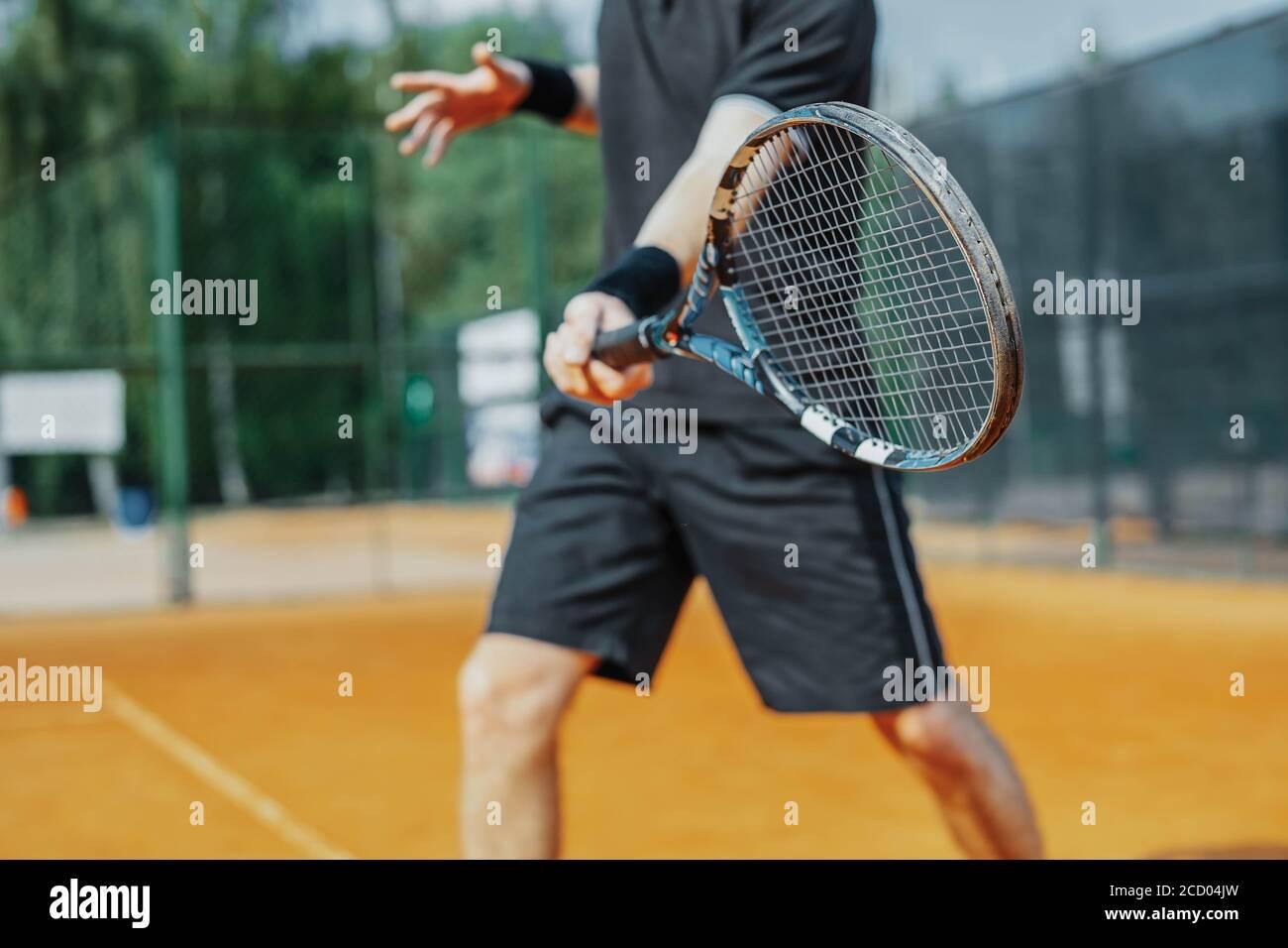 Gros plan de l'homme jouant au tennis sur le court et battant le ballon avec une raquette. Le joueur frappe le ballon avec une raquette pendant qu'il joue au match Banque D'Images