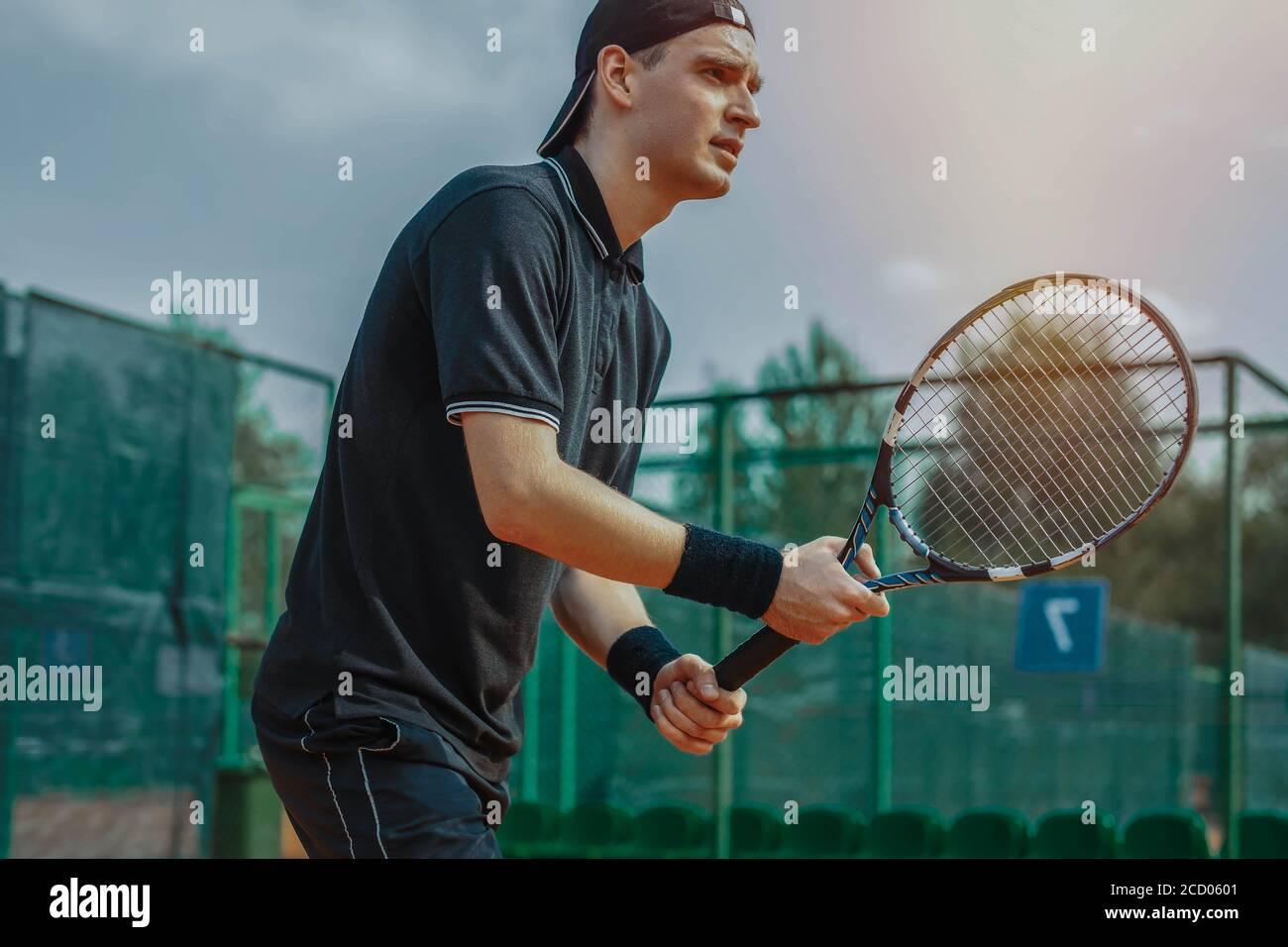 Gros plan de l'homme tenant une raquette dans les deux mains pour frapper en hauteur tout en attendant que le ballon sert au court de tennis. Banque D'Images