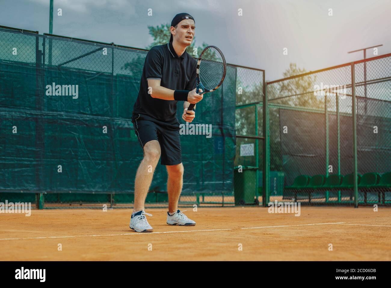 Plan lointain de l'homme tenant raquette dans les deux mains à Tendez la grève en attendant que le ballon soit servi sur le court de tennis Banque D'Images