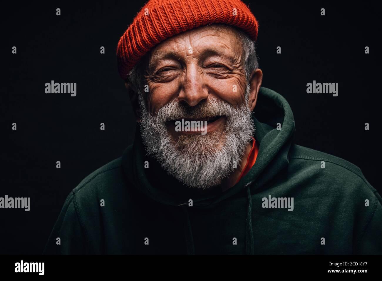 Portrait en gros plan d'un optimiste heureux de 70 ans au visage ridé souriant, vêtu d'un chapeau orange et d'un sweat à capuche vert hipster, isolé sur une bande noire Banque D'Images