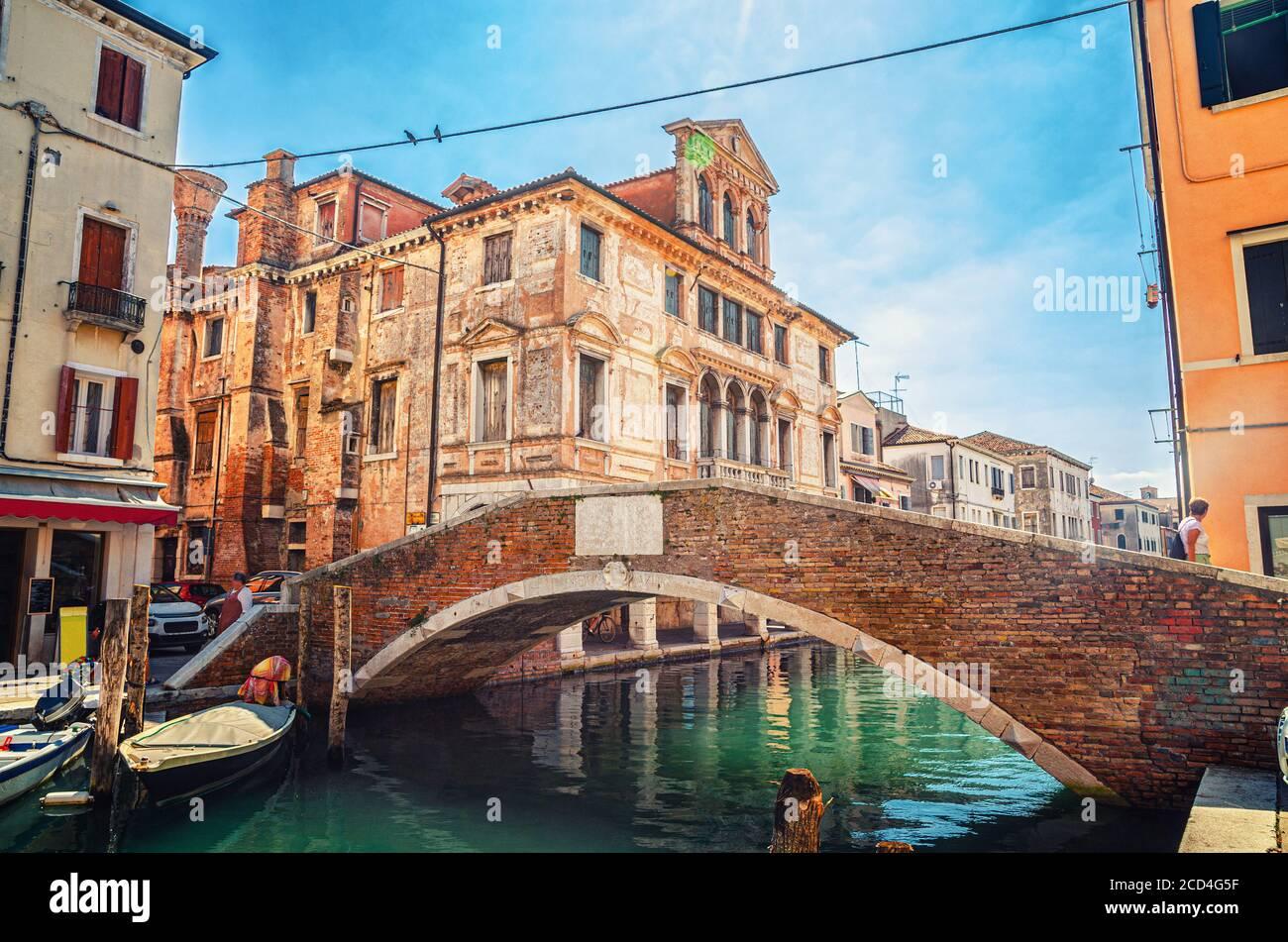 Pont en pierre Ponte Caneva traversant le canal de Vena avec des bateaux amarrés et un vieux bâtiment dans le centre historique de la ville de Chioggia, ciel bleu en été, région de Vénétie, Italie du Nord Banque D'Images