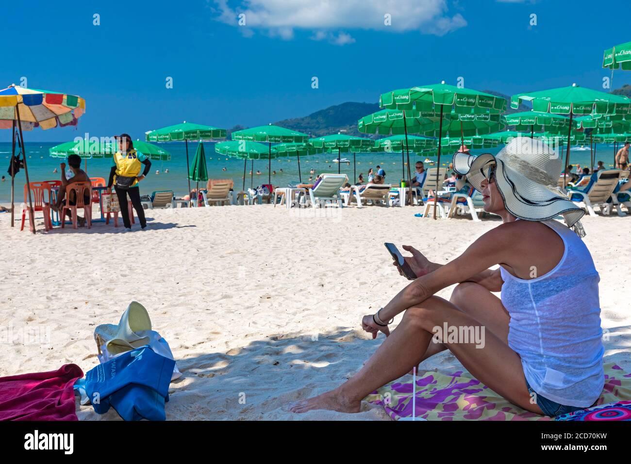 Touriste utilisant le téléphone portable à l'ombre sur la plage, Patong, Phuket, Thaïlande Banque D'Images