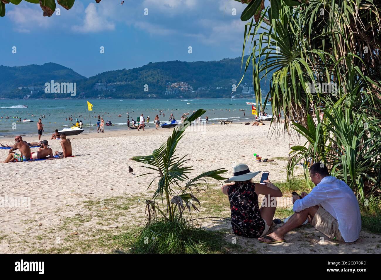 Couple touristique sur les téléphones portables à l'ombre à Patong Beach, Phuket, Thaïlande Banque D'Images